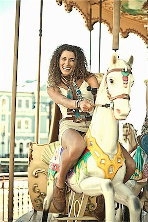 Young woman riding carousel Stock Photo - Premium Royalty-Free, Code: 649-07436334