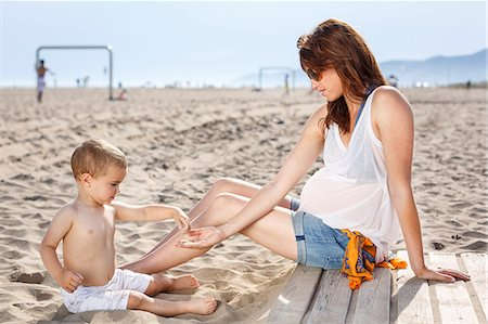 Baby on beach tipping sand onto mother's hand Stock Photo - Premium Royalty-Free, Code: 649-07436386