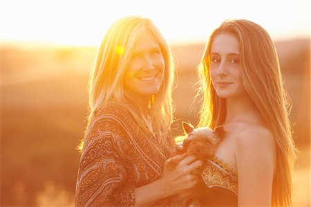 Woman and teenager standing in field at dusk holding domestic dog Stock Photo - Premium Royalty-Free, Code: 649-07436498