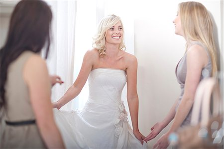 Young woman trying on wedding dress, with friends Stock Photo - Premium Royalty-Free, Code: 649-07436518
