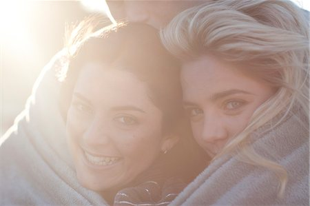 Three friends huddled up in blanket Stock Photo - Premium Royalty-Free, Code: 649-07436563