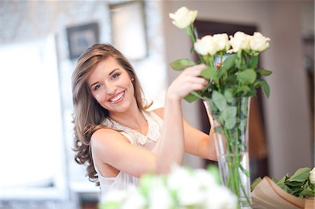 Portrait of young woman arranging roses Stock Photo - Premium Royalty-Free, Code: 649-07436587