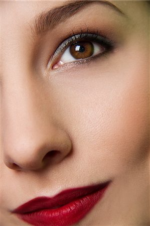 Cropped studio portrait of young woman's eye and lips Stock Photo - Premium Royalty-Free, Code: 649-07436633