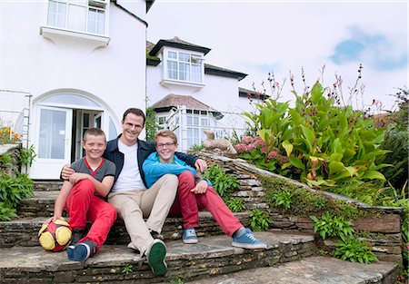 Father and sons sitting on steps in garden Stock Photo - Premium Royalty-Free, Code: 649-07436681