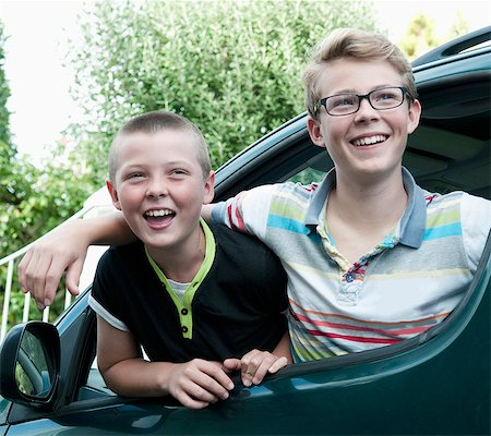 Portrait of two brothers leaning out of car window Stock Photo - Premium Royalty-Free, Code: 649-07436690