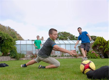 preteen boys playing - Father and sons playing football in garden Stock Photo - Premium Royalty-Free, Code: 649-07436691