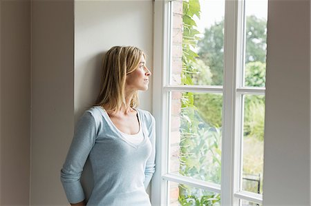 Portrait of mid adult woman looking out of window Stock Photo - Premium Royalty-Free, Code: 649-07436838