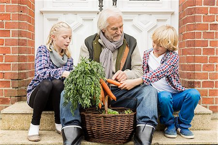 preteens pictures older men - Grandfather sitting with grandchildren on doorstep with carrots Stock Photo - Premium Royalty-Free, Code: 649-07436847