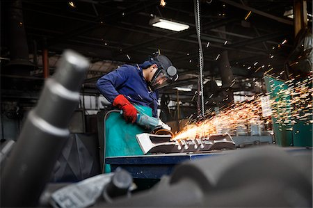 """Forge worker grinding (or linishing) flight bar (mining component), removing last traces of excess """"flash"""" not removed by clipping press Stock Photo - Premium Royalty-Free, Code: 649-07436899"""