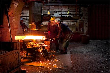 people working in factory - Forge workers pre form red hot billet into flight bar (mining component) on hammer Stock Photo - Premium Royalty-Free, Code: 649-07436911