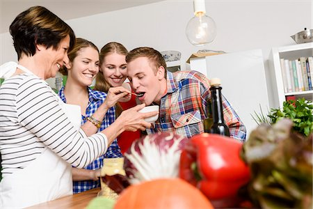 Mother, daughters and son tasting food Stock Photo - Premium Royalty-Free, Code: 649-07436929
