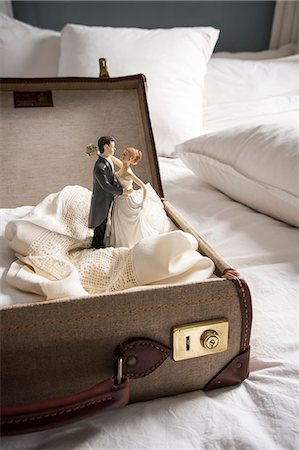 Open suitcase on bed with wedding figurines Stock Photo - Premium Royalty-Free, Code: 649-07437014
