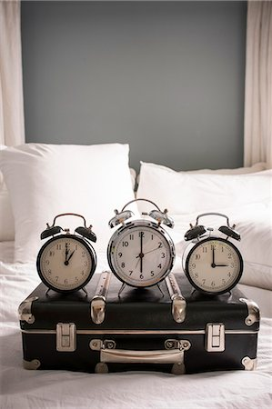 Closed suitcase on bed with three alarm clocks Stock Photo - Premium Royalty-Free, Code: 649-07437017