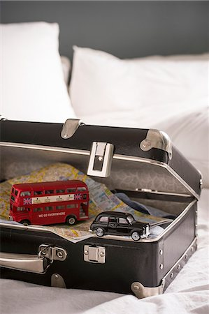 remembered - Open suitcase on bed with toy London bus and black cab Stock Photo - Premium Royalty-Free, Code: 649-07437018