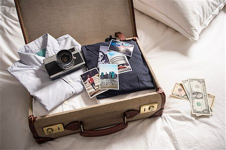 Open suitcase on bed with camera and photographs Stock Photo - Premium Royalty-Free, Code: 649-07437011
