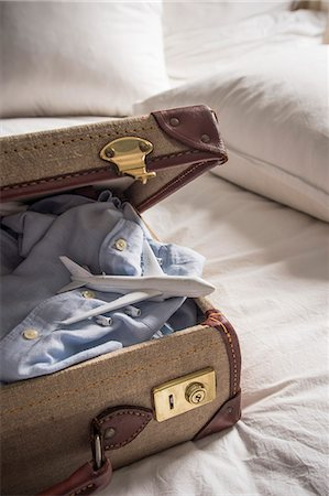 still life - Open suitcase on bed with shirt and toy airplane Stock Photo - Premium Royalty-Free, Code: 649-07437013