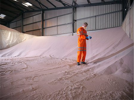 Worker in reflective clothing inspecting zircon sand Stock Photo - Premium Royalty-Free, Code: 649-07437042