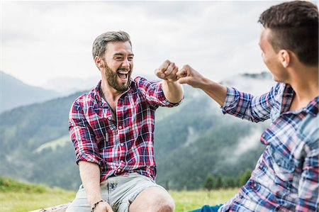 Two male friends sitting on fence, Tyrol Austria Stock Photo - Premium Royalty-Free, Code: 649-07437130