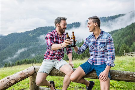 Two male friends drinking beer on fence, Tyrol Austria Foto de stock - Sin royalties Premium, Código: 649-07437131