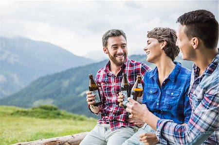 friendship - Three young adult friends drinking beer on fence, Tyrol Austria Stock Photo - Premium Royalty-Free, Code: 649-07437132
