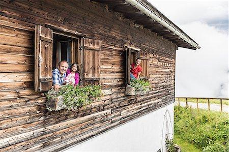 Portrait of family at chalet windows, Achenkirch,  Tyrol, Austria Stock Photo - Premium Royalty-Free, Code: 649-07437142
