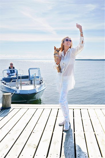 Young woman photographing herself with dog on pier, Gavle, Sweden Stock Photo - Premium Royalty-Free, Image code: 649-07437170