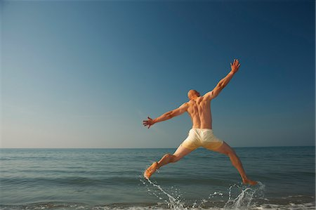 Mid adult man jumping outstretched over sea Stock Photo - Premium Royalty-Free, Code: 649-07437187