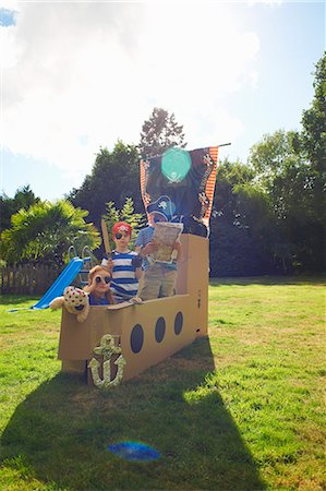 playing - Two brothers and sister playing in garden with homemade pirate ship Stock Photo - Premium Royalty-Free, Code: 649-07437207