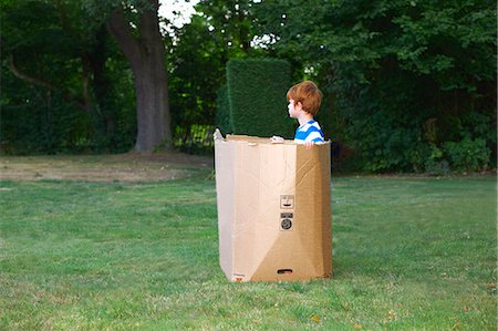 Young boy watching from cardboard box in garden Stock Photo - Premium Royalty-Free, Code: 649-07437210