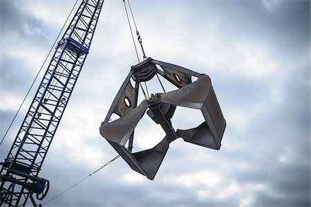 Low angle view of crane grab against cloudy sky Stock Photo - Premium Royalty-Free, Code: 649-07437243