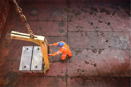 High angle view of worker unloading metal alloy ingots from ship's hold Stock Photo - Premium Royalty-Free, Code: 649-07437266