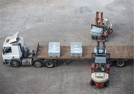 High angle view of fork lift trucks  loading alloy ingots onto transport Stock Photo - Premium Royalty-Free, Code: 649-07437274