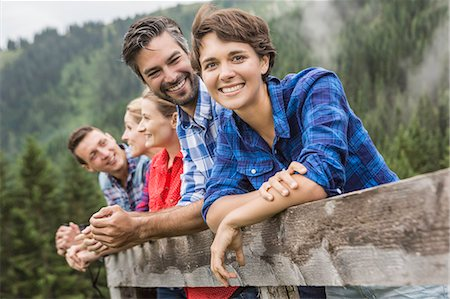 Group of friends leaning on wooden fence, Tirol, Austria Stock Photo - Premium Royalty-Free, Code: 649-07437306