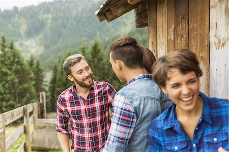 Group of friends chatting behind wooden shack Stock Photo - Premium Royalty-Free, Code: 649-07437316