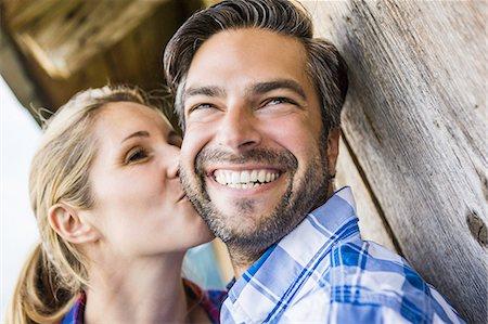 Woman kissing man's cheek outside wooden shack Stock Photo - Premium Royalty-Free, Code: 649-07437325