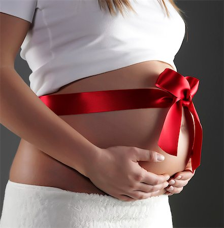 portrait of pregnant woman - Pregnant woman's belly with red gift bow Stock Photo - Premium Royalty-Free, Code: 649-07437406