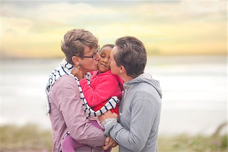 Gay couple hugging adopted child Stock Photo - Premium Royalty-Free, Code: 649-07437425