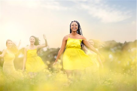 Girls in yellow dancing on meadow Stock Photo - Premium Royalty-Free, Code: 649-07437433