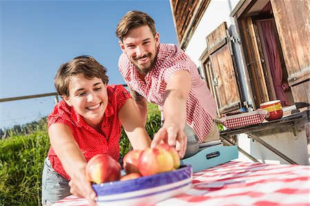 Young couple with apples outside chalet, Tyrol, Austria Stock Photo - Premium Royalty-Free, Code: 649-07437517