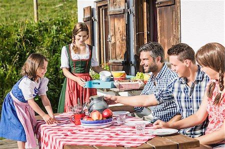 Friends enjoying breakfast outside chalet, Tyrol, Austria Stock Photo - Premium Royalty-Free, Code: 649-07437529