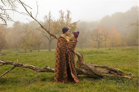 Young couple wrapped in blanket in misty park Stock Photo - Premium Royalty-Free, Code: 649-07437637