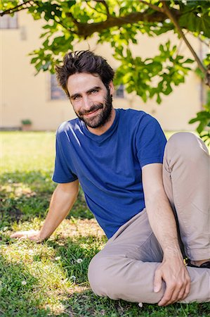 Portrait of mid adult man sitting on grass Stock Photo - Premium Royalty-Free, Code: 649-07437644