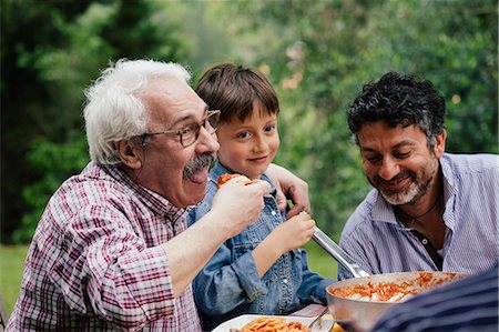 Senior man enjoying food with grandson and son Stock Photo - Premium Royalty-Free, Code: 649-07437658