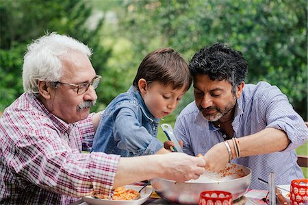 Three generations of male family enjoying a meal together Stock Photo - Premium Royalty-Free, Code: 649-07437659