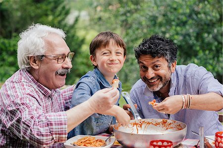 Boy enjoying a meal together with father and grandfather Stock Photo - Premium Royalty-Free, Code: 649-07437660