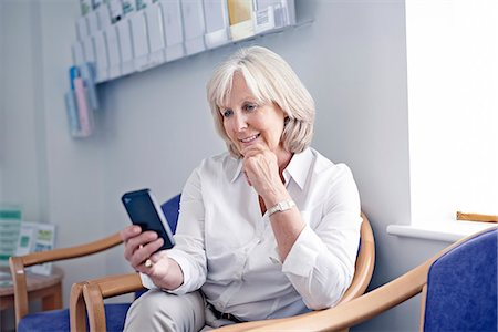Mature female patient looking at mobile phone in hospital waiting room Stock Photo - Premium Royalty-Free, Code: 649-07437694