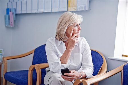 Mature female patient with mobile phone in hospital waiting room Stock Photo - Premium Royalty-Free, Code: 649-07437695