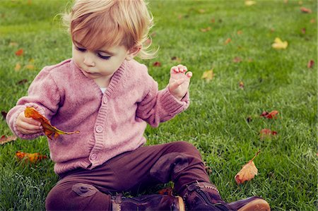Toddler sitting on grass looking at autumn leaf Stock Photo - Premium Royalty-Free, Code: 649-07437729