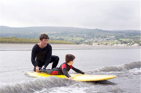 family active beach - Father teaching son how to surf Stock Photo - Premium Royalty-Free, Code: 649-07437741