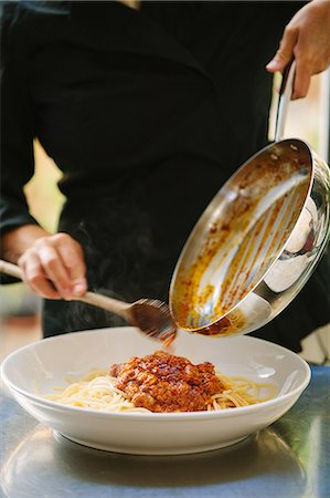 delicious - Close up of woman scraping bolognese sauce from pan to plate Stock Photo - Premium Royalty-Free, Code: 649-07437756